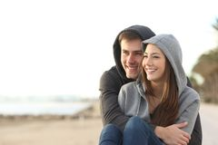 Couple of teens looking at horizon on the beach. Happy couple of teens hugging and looking at horizon on the beach Stock Photo