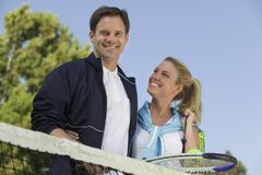 Couple at Tennis Net. Portrait, low angle view royalty free stock image