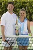 Couple at Tennis Net with Trophy portrait Royalty Free Stock Photos