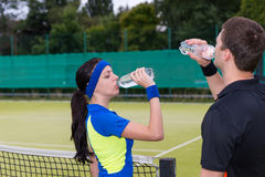 Couple of tennis players drinking water after match outdoor Stock Photos