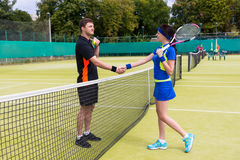 Couple of a tennis players shaking hands over the net Royalty Free Stock Image