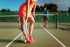 Couple with tennis rackets plays on outdoor court. Young couple with tennis rackets plays on outdoor court. Summer season active sport game stock photography