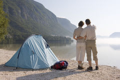 Couple beside a tent at a mountain lake Stock Photo
