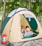 Couple in tent using laptop Stock Photography