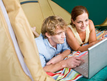 Couple in tent using laptop Stock Photo