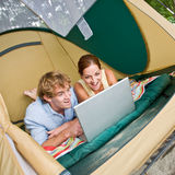 Couple in tent using laptop Royalty Free Stock Images