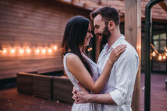 Couple on terrace. Beautiful romantic couple on house`s terrace. Hugging, smiling and enjoing the company of each other royalty free stock image