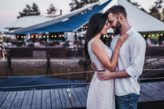 Couple on terrace. Beautiful romantic couple on house`s terrace. Hugging, smiling and enjoing the company of each other royalty free stock photography