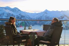 A couple on the terrace of a cafe in the mountains, in winter. Zell am See, Austria. Zell am See, Austria - December 31, 2017: A couple on the terrace of a cafe royalty free stock photos