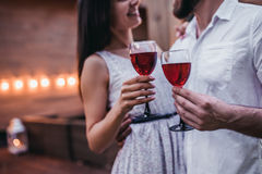 Couple on terrace. Cropped image of beautiful romantic couple on house`s terrace. Drinking wine, hugging, smiling and enjoing the company of each other stock image