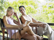 Couple On Terrace With Woman Reading Book Stock Photography