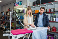 Couple Testing Iron By Ironing Shirt In Hypermarket Stock Images