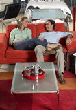 Couple testing new red sofa in furniture store, woman sitting with feet up on man's lap, smiling Royalty Free Stock Photos