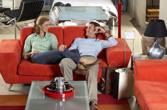 Couple testing new red sofa in furniture store, woman sitting with feet up on man's lap, smiling Stock Photo