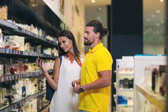 Couple testing perfumes and fragrances. At cosmetics store Royalty Free Stock Photos