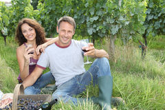 Couple testing wine in vineyard. Closeup of couple of winegrowers drinking wine during vintage season Royalty Free Stock Images
