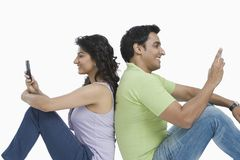 Couple text messaging on mobile phones Stock Images