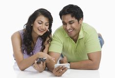 Couple text messaging on mobile phones Royalty Free Stock Photo