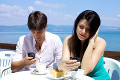 Couple texting having breakfast in front of lake Royalty Free Stock Photos