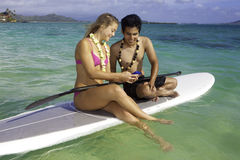 Couple texting on a paddle board Royalty Free Stock Photos