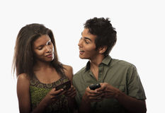 Couple texting with their cell phones Royalty Free Stock Photos