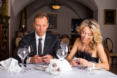 Couple texting during their date Stock Image