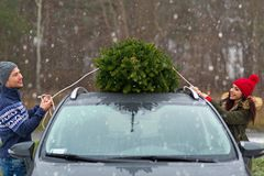 Couple with their Christmas tree on roof of the car Stock Photo