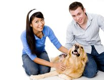 Couple And Their Dog. A young couple stroke their dog - shot in studio on white background Royalty Free Stock Photo