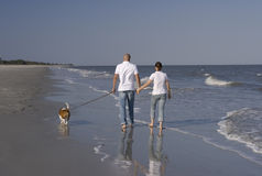 A Couple with Their Dog. A couple walking on a beach, with their dog on a leash Royalty Free Stock Photography