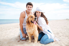 Couple with their dog on the beach in summer. Beautiful young couple with their dog on the beach in summer Royalty Free Stock Photography