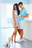 Couple with their dog in the kitchen at home. Young cheerful couple spending leisure time together with their dog in the kitchen at home Stock Photos