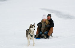 Couple and their dog play in snow. Couple rides a sledge and their dog costs ahead. A dog - Siberian huskies Royalty Free Stock Photography