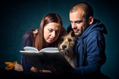 Couple and their dog reading a book. Studio portrait of a couple and their cute adopted half breed dog taken while they are reading a book Royalty Free Stock Photo