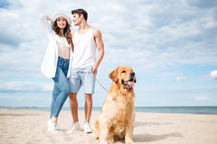 Couple and their dog standing on the beach. Happy young couple and their dog standing on the beach Stock Images