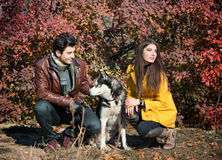 Couple with their dog. Young couple with their husky dog resting in autumn countryside Royalty Free Stock Photo