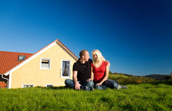 Couple and their home. Young couple sitting in front of their country home on the lawn in the sun Stock Images