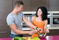 Couple in their kitchen with salad Royalty Free Stock Images
