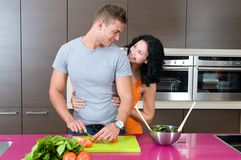 Couple in their kitchen with salad Stock Images
