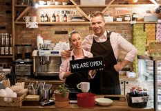 Couple in their new cafe, proud news business owners. Young couple in their new cafe, proud news business owners royalty free stock image