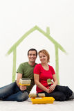 Couple in their new home painting Stock Photos