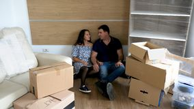 Couple in their new house lying in the floor. Surrounded by cardboard boxes because they just moved in. New beginnings stock video footage