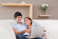 Couple with their notebook on the sofa Royalty Free Stock Images