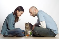 Couple with their Pets. A young couple sit on the floor, enjoying their two pets, a cat and a gold fish Stock Image