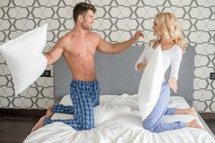 Couple in their sleepwear having a pillow fight Stock Photo