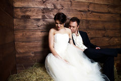 Couple in their wedding clothes in barn with hay Stock Images