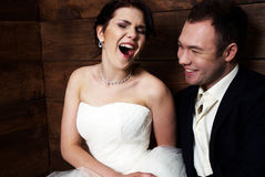 Couple in their wedding clothes in barn laughing Stock Images