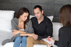Couple therapy indoor. Young women and men on couple therapy, indoor. Holding each other hands Stock Photo