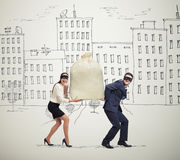Couple of thieves carrying bag. Funny picture of happy couple of thieves carrying bag and looking at camera in drawing street Royalty Free Stock Photography