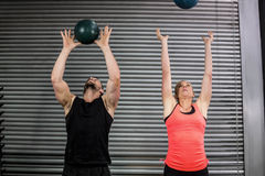 Couple throwing ball in the air Stock Image