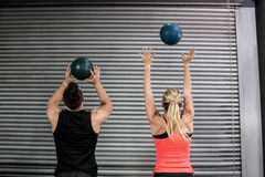 Couple throwing ball in the air Royalty Free Stock Photos